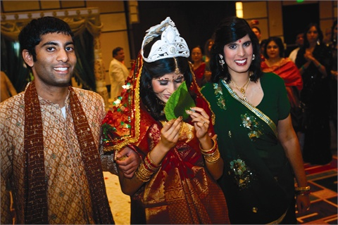 "<p>Traditionally, a Bengali-Hindu bride's face must be covered for the first portion of the ceremony, until the ""shubha dristi"" or ""first glance."" Some brides might be bummed, but I was happy guests could admire my glistening red-and-gold nails as I clutched the deep green paan leaves that covered my face. <em>Wedding photography by Slava Slavik Photography</em></p>"