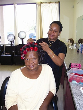 <p>Student Vanessa Valley, who heard of the school through word-of-mouth, does client Jean James' hair.</p>