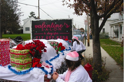 <p><em>Employees Trinity Ricker (foreground) and Ashley Link help ­prepare the Valentine's Salon & Spa float for Greencastle's annual Christmas parade. </em></p>