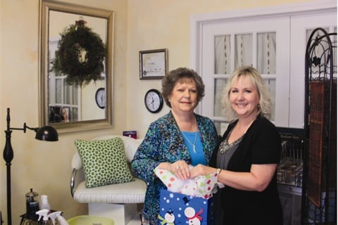 """<p><em>European Body Wraps owner Vickie Foster (right) hands 13-year patron Brenda Carter a holiday gift bag. """"I feel like I get extra special treatment during the holidays,"""" says Carter, """"Even though I get special treatment every time I come in for a service. The extra thought really heightens my holiday spirit.""""</em></p>"""