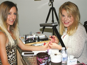 <p>Model Ciara Pisa patiently went in and out of the LED light as cover tech Elsbeth Schuetz (right) worked on her elaborate holiday designs.</p>
