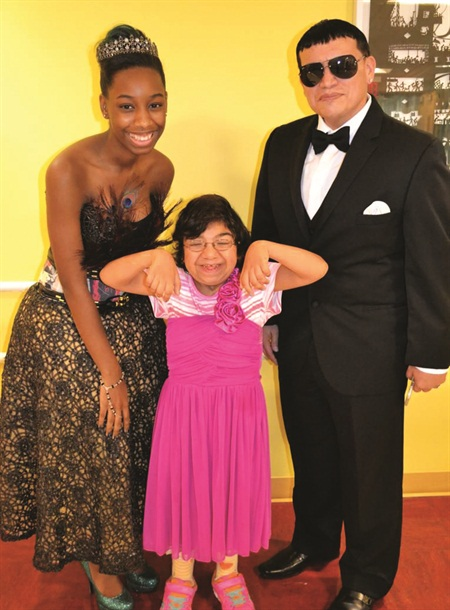 <p>Polished Girlz founder Alanna Wall and Mr. Luis pose with a prom-goer.</p>