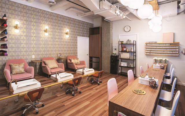 The salon's pink and gold furniture complements the sleek wood floors and muted walls.
