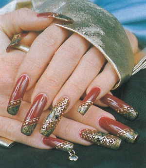 <p>Natalie Kurz's own hands display the elegant nail art she does herself, complete with 84 stones and a dangling nail charm. </p>