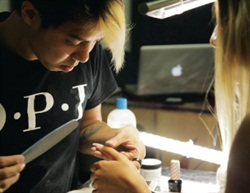<p>Robert Nguyen checks his model's nail shape for precision before getting to the design.</p>