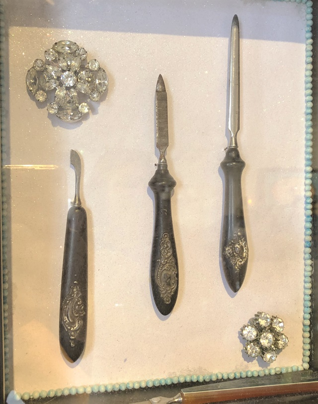 <p>In addition to medals and fun photos lining the walls, this vintage manicure set is also used for decoration.</p>