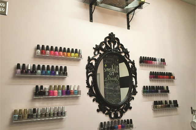 <p>The wall behind the pedicure couch has shelves for polish, NAILS Magazines, and the pair's licenses. They wanted their licenses to be visible, yet not show their addresses.</p>