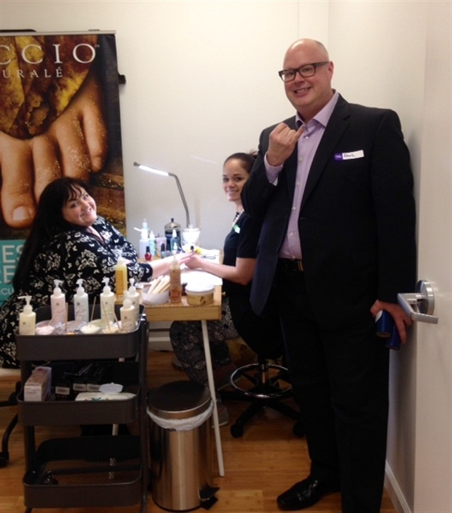 <p>Director of education Anita Lumpkin enjoys a nail art demo from Cuccio educator Marilyn Garcia, while Learning Center director Paul Jablonski shows off his own nail demo.</p>