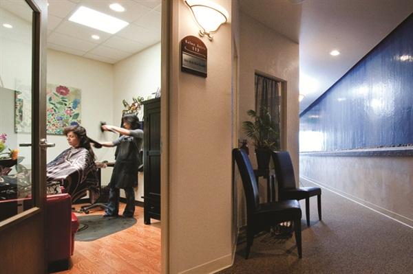 <p>A stylist and client enjoy privacy in a Phenix Salon Suite.</p>