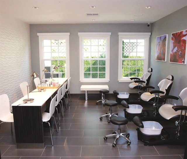 A dedicated pedicure room offers a serene, clean environment with dark gray tiled floors and white walls. The chairs, also by Belava, feature the company's signature bowls with disposable liners.