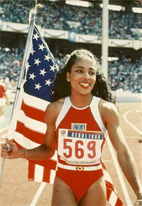 Flo-Jo at the 1996 Olympics carry the flag and showing off what became her signature nail look.