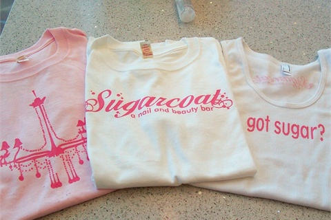 <p>These cute tees showcase the salon's iconic chandelier, the distinctive logo, and a clever catchphrase.</p>