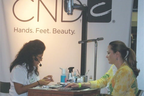 Nail tech Lisa Wong instructs trade show attendees in the CND booth — this is where you'll find her most often.