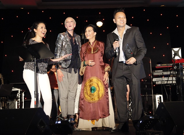 <p>VietSALON managing editor Anh Tran, CND co-founder and style director Jan Arnold, and CND brand ambassador Kieu Chinh present Tan Nguyen with the trophy for his winning nail art mural.</p>