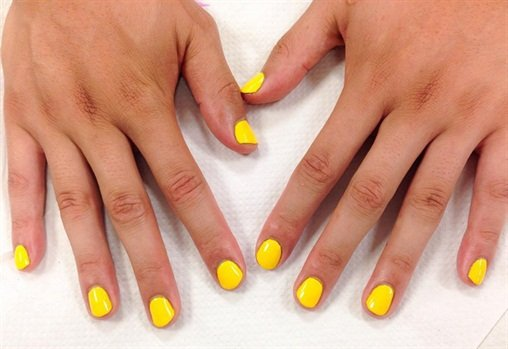 My first spa manicure was topped with a bright yellow polish change.