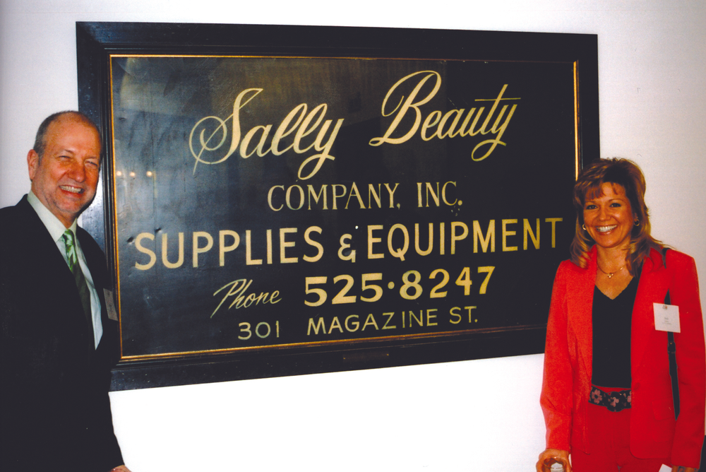 <p>Sally Beauty Company has come a long way in 40 years since the first store opened in New Orleans. Here Emmett and Beth Hickey stand by one of the original store signs in the new Sally headquarters in Denton, Texas.</p>