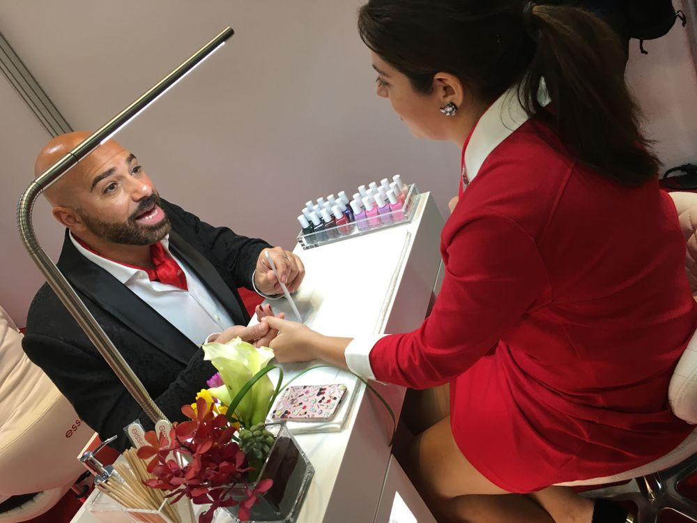 <p>Gino Trunzo demoed Gel Couture on senior editor Beth Livesay at the Essie booth</p>