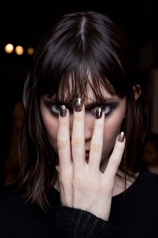 <p>Katie Jane Hughes used butter London Union Jack Black and a fan brush to make a windshield wiper texture on the nail, and finshed with gold foil at Tadashi Shoji</p>