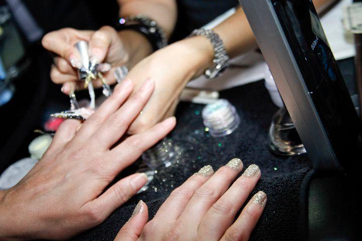 <p>Beautiful Nails educator Sindy Mark starts the glitter process on Hollyscoop host Crystal Marie Denha.</p>