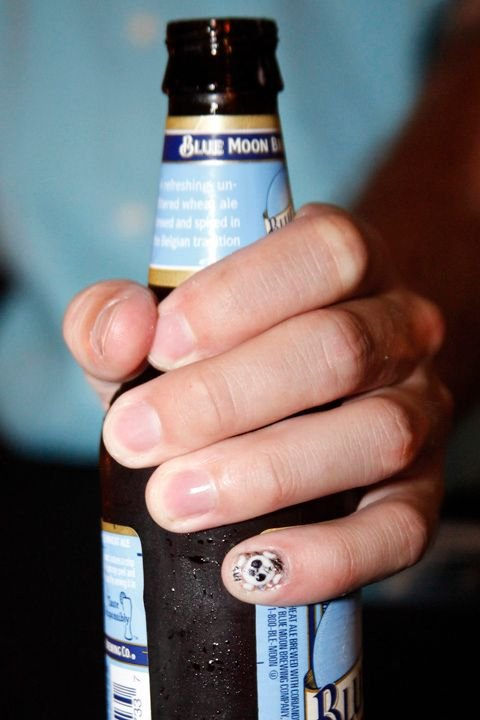 <p>With beer in hand, NAILS Magazine senior editor Tim Crowley shows off his acrylic skull nail.</p>