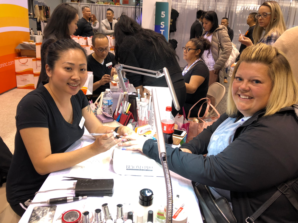 <p>Jasmine Quach (left) demoed crystal application over cat eye nails on Heather Mitilicen at the NuRevolution booth.</p>