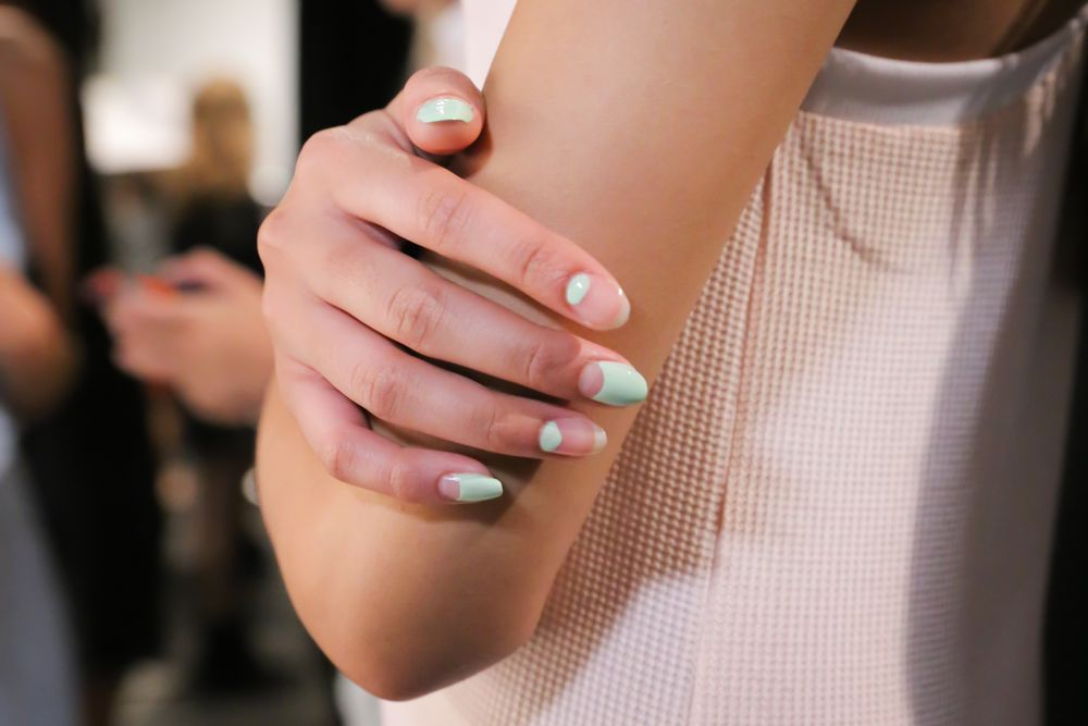 <p>OPI joined Charlotte Ronson at Lincoln Center for the designer's Spring/Summer 2015 presentation. Lead nail artist Miss Pop created a nail look showcasing negative space, with alternating cutout half moon shapes. Photo courtesy of OPI.&nbsp;</p>