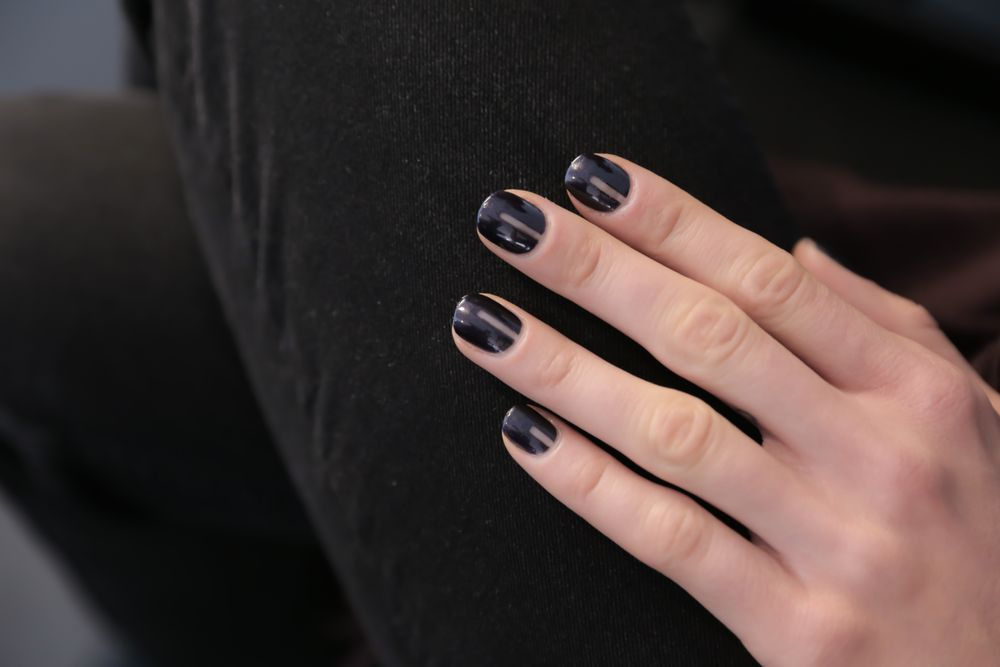 <p>A strip of tape is all you need to protect nails under two coats of OPI Light My Sapphire. Thie negative space look showed at Marissa Webb.</p>