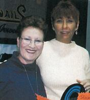 <p>With the help of educator Sandi Kirshen, Snails CEO Marlene Sortino (right) shows off some of her company's extensive jewelry and nail art line.</p>