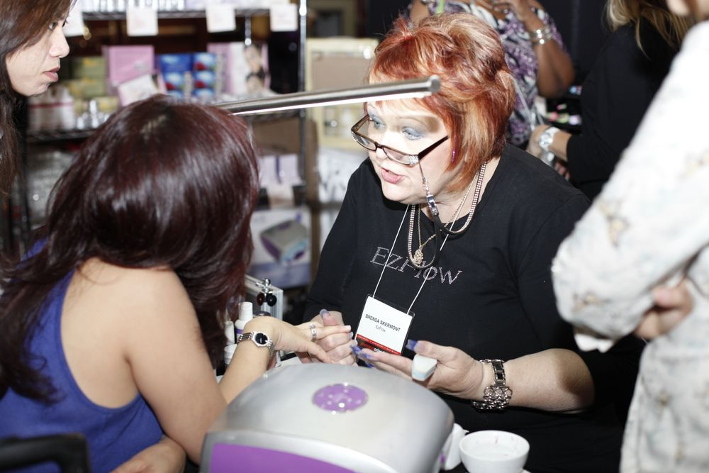 <p>EZ Flow&rsquo;s Brenda Skermont talks nails with a show attendee.</p>