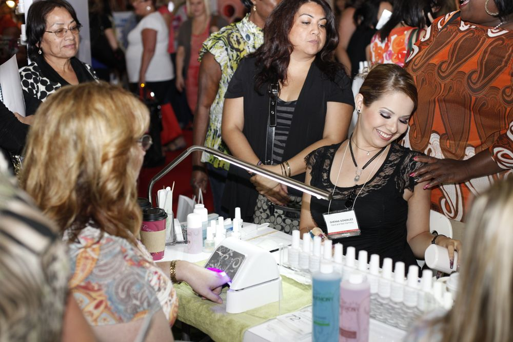 <p>Hand &amp; Nail Harmony educator Ghenna Gonzalez shows Melinda Lane and the curious crowd of attendees ways to use Gelish to create nail art.</p>