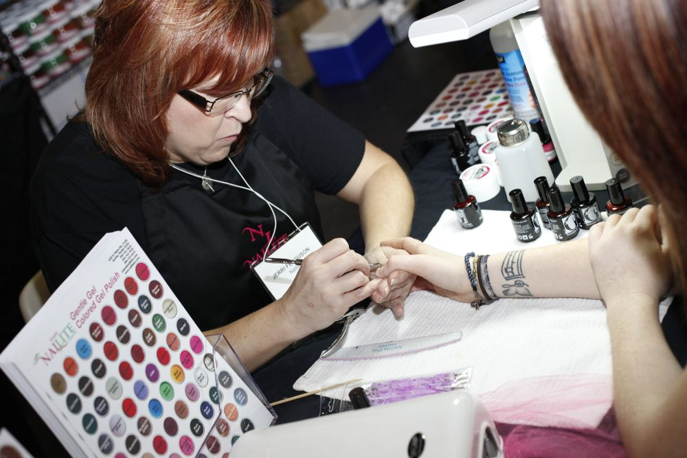<p>Jerri Ferguson, an educator for Nailite, preps Cara Smith&rsquo;s nails for application of Nailite&rsquo;s new gel polish, GIA, or Gels in Action.</p>