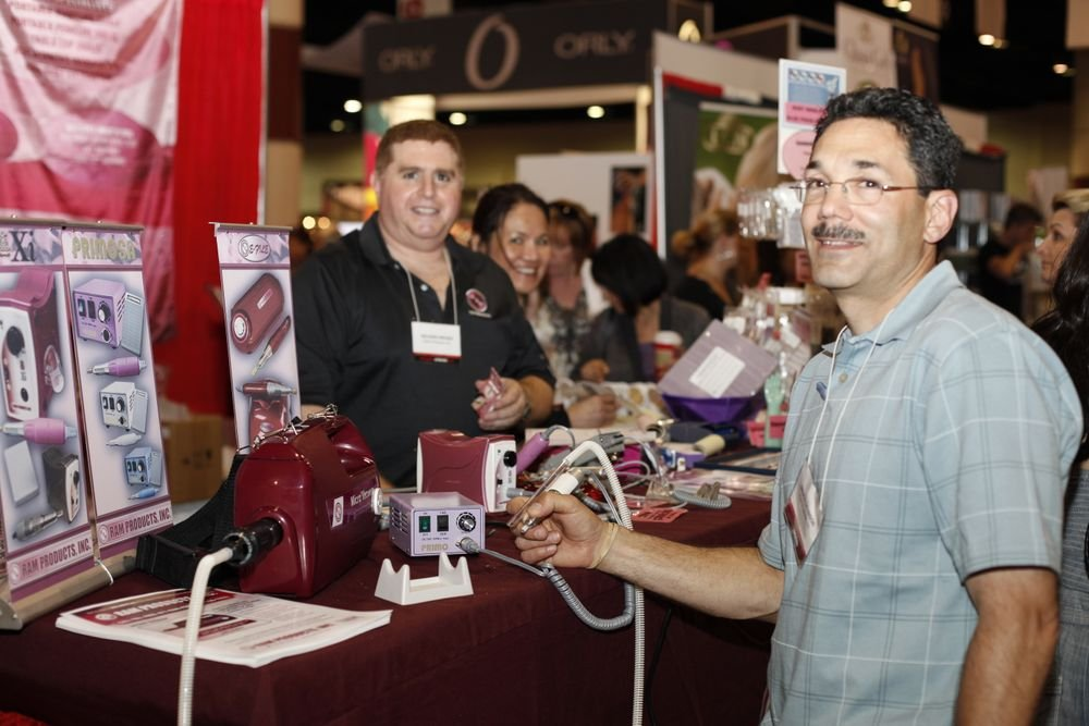 <p>Bruce Levinson demonstrates how to hold the new RPM Nail Dust Vacuum from RAM Products. Ram Products owner Richard Wiesen and Cynthia Wiesen were all smiles in the background.</p>