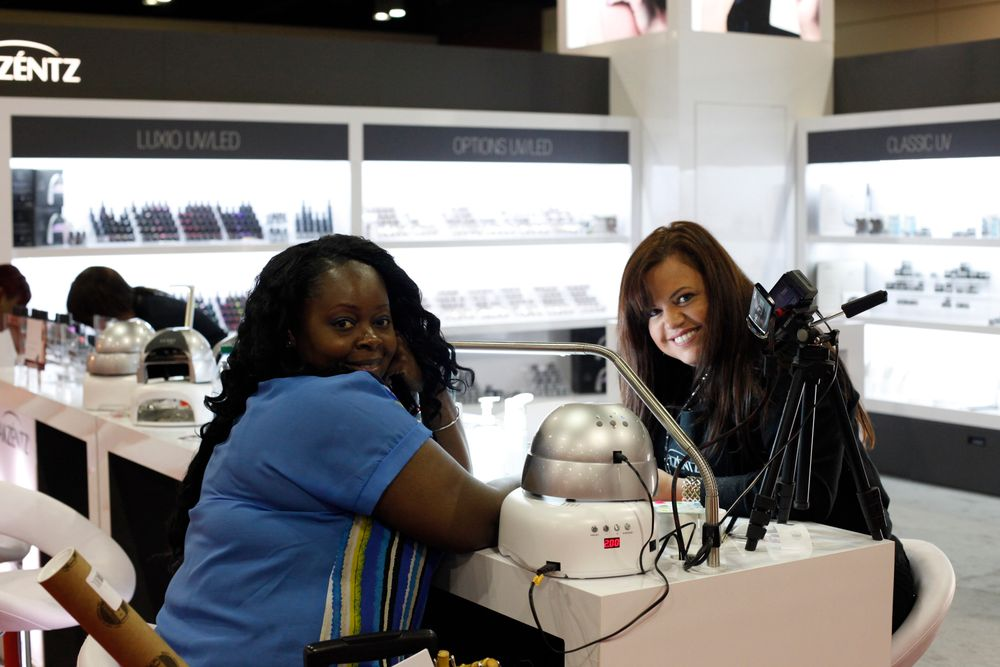 <p>Narissa Moss from Renew Day Spa in the Bahamas visits the Akzentz booth with educator Jesica Hoel.</p>