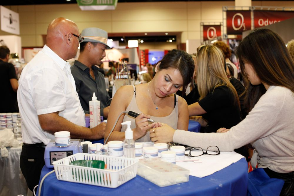 <p>NexGen Nails educator Mary Le demos the company's acrylic product on a show attendee.</p>