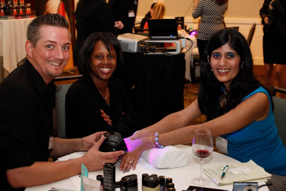 <p>NAILS managing editor Sree Roy (right) chats with Alessandro's LeShaun Brown-Glenn and gets her nails done by educator and international competitor, Frank.</p>