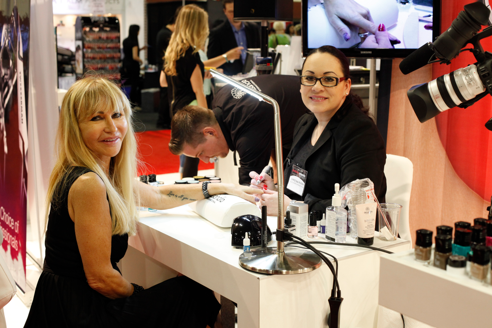 <p>Alessandro founder and CEO Sylvia Troska gets her nails done by Alessandro international trainer Christina Rivera in her favorite shade of Striplac color, Love Secret. This was the company's first tradeshow in the U.S.</p>