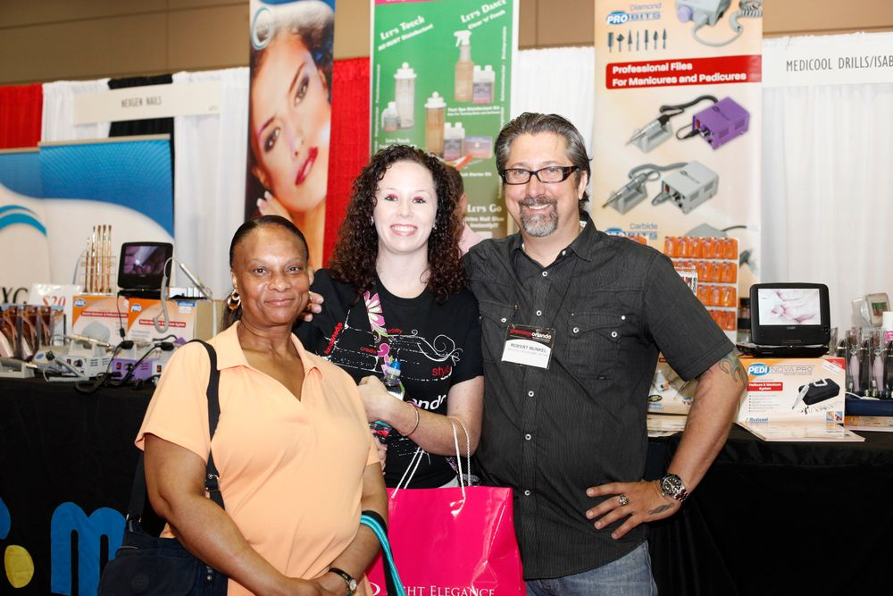 <p>Medicool's Robert Munkel (right) talks to Ann Marie Alexander (left) and Regina Beaird about the nail industry.</p>