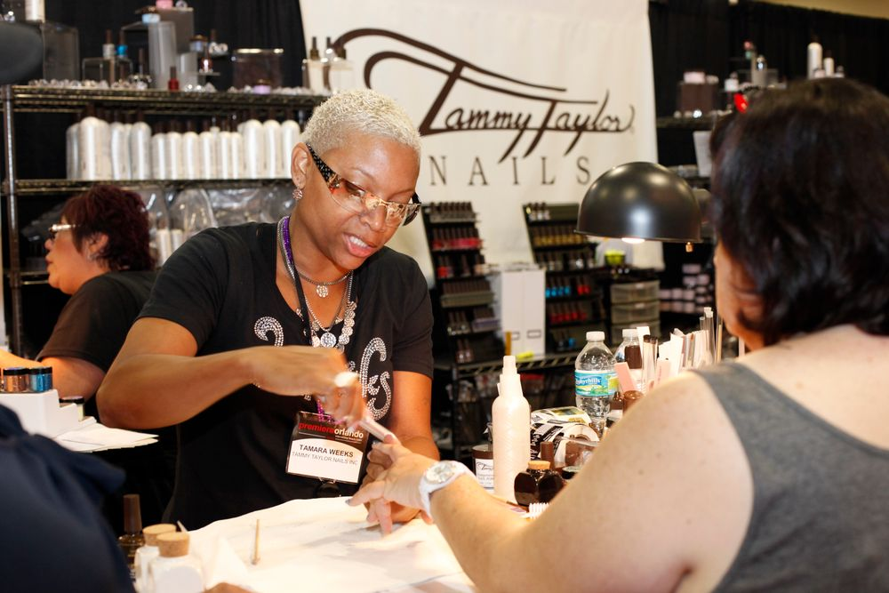 <p>Tamara Weeks, educator for Tammy Taylor Nails, preps an attendees nails during a product demo.</p>