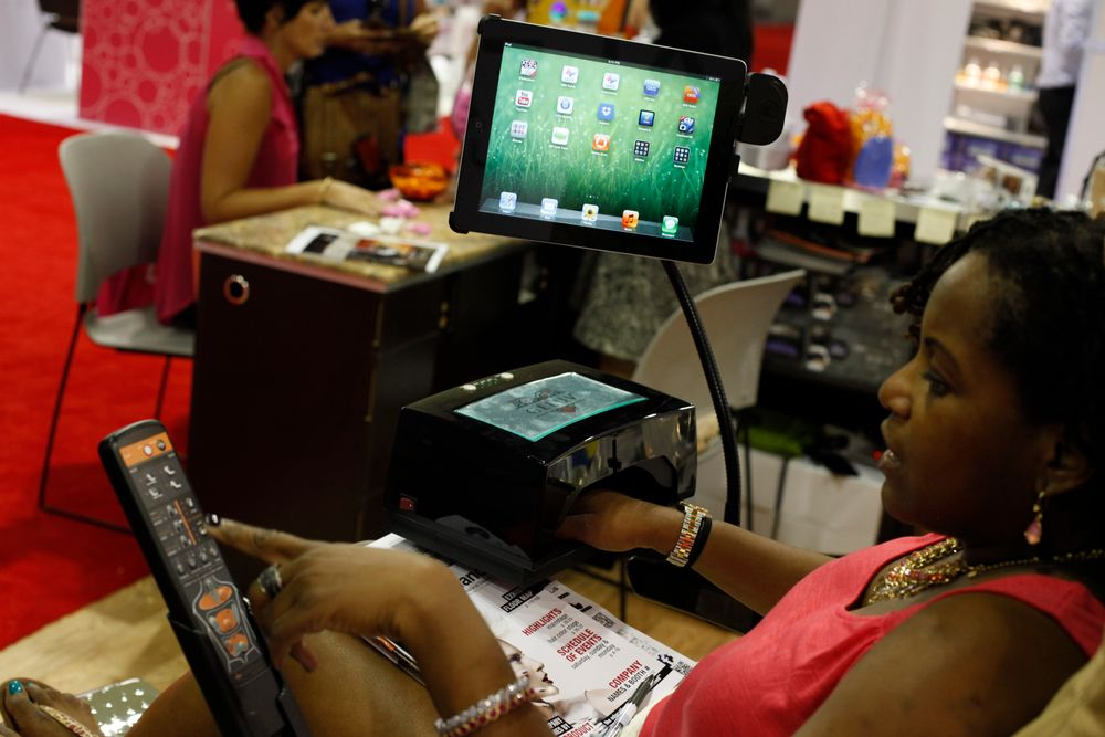 <p>A show attendee tries Alfalfa Nail Supply&rsquo;s new VersaTray that holds a UV lamp and iPad.</p>