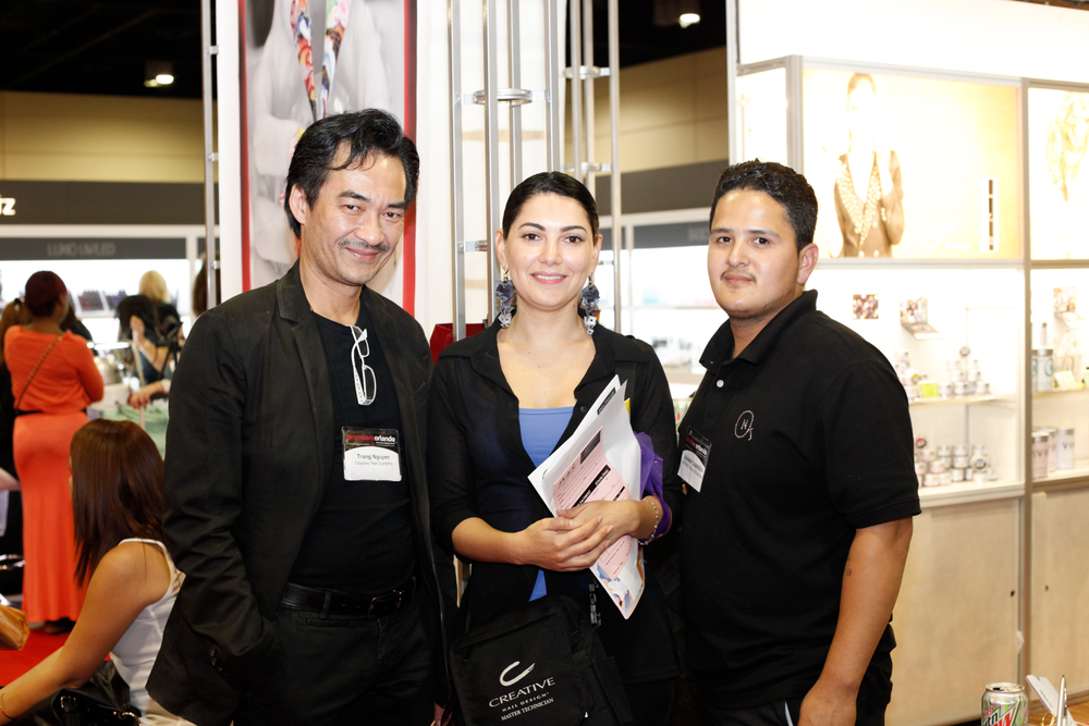 <p>Odyssey Nail Systems&rsquo; Trang Nguyen (left) and Johnny Cabrera (right) talked with Chile-based Ana Maria Gomez.</p>