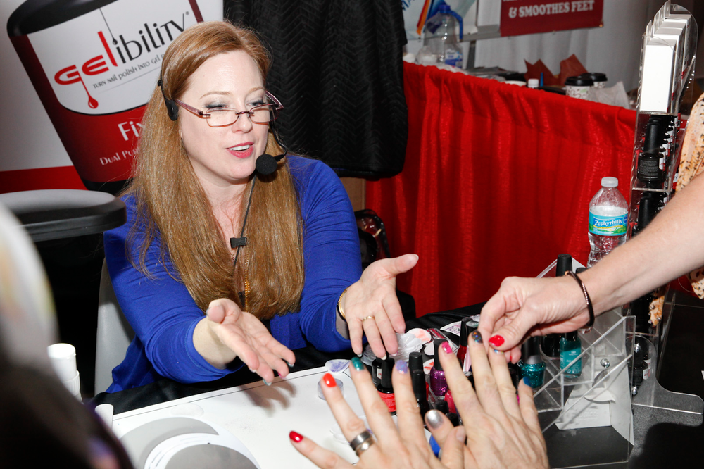 <p>Gelibility owner Brandi Hensley shows an attendee how to turn regular polish into gel-polish.</p>