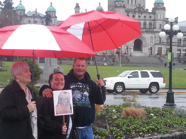<p>Tami Schmidt, JoAnne Sandyke, and Stanley Sandyke with a photo stick of Vicki touring Victoria, B.C.</p>