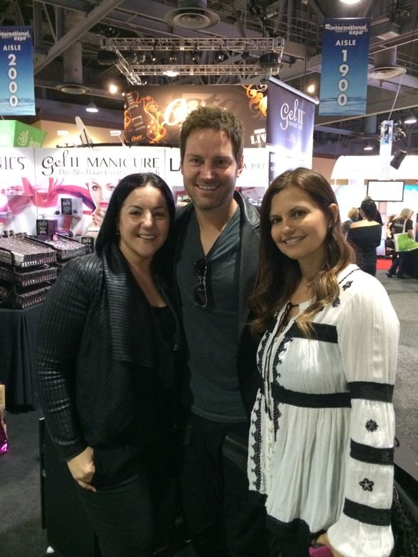 <p>Celebrity nail techs Elle and Tom Bachik (with his wife, Liz, on the right) caught up at the Gel II booth.&nbsp;</p>