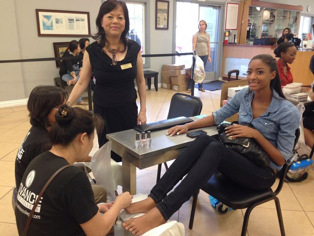 <p>Advance Beauty College instructor Cindy Nguyen offers advice as students perform a pedicure on a model.</p>