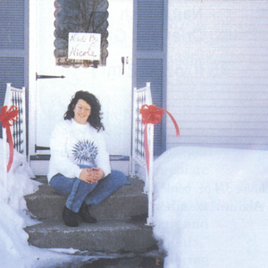 Nicole Forest sits on her salon's dorrstep after having cleared out mounds of snow so clients...