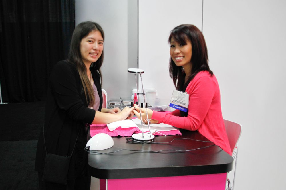 <p>VietSALON associate editor Kim Pham getting a demo of one of Dashing Diva's new DesignFX appliqu&eacute;s, applied by educator So Yong Yu.</p>