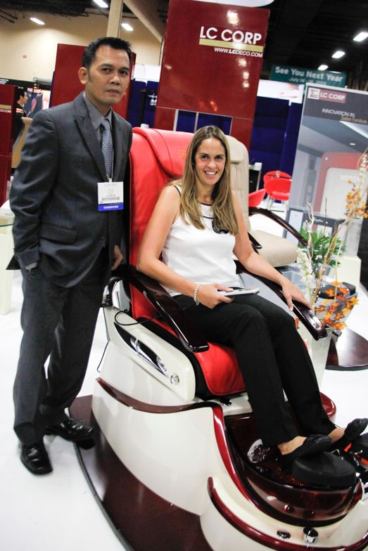 <p>LC Corp's Hieu Le shows Mary Baughman one of LC Corp's SpaZi pedicure chairs.</p>