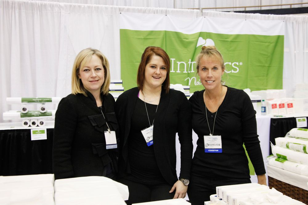 <p>Intrinsics' Lea Anne Cook, Erin Haggerty, and Stacy Glover helped show attendees find the perfect cotton and towel products to use in their services.</p>