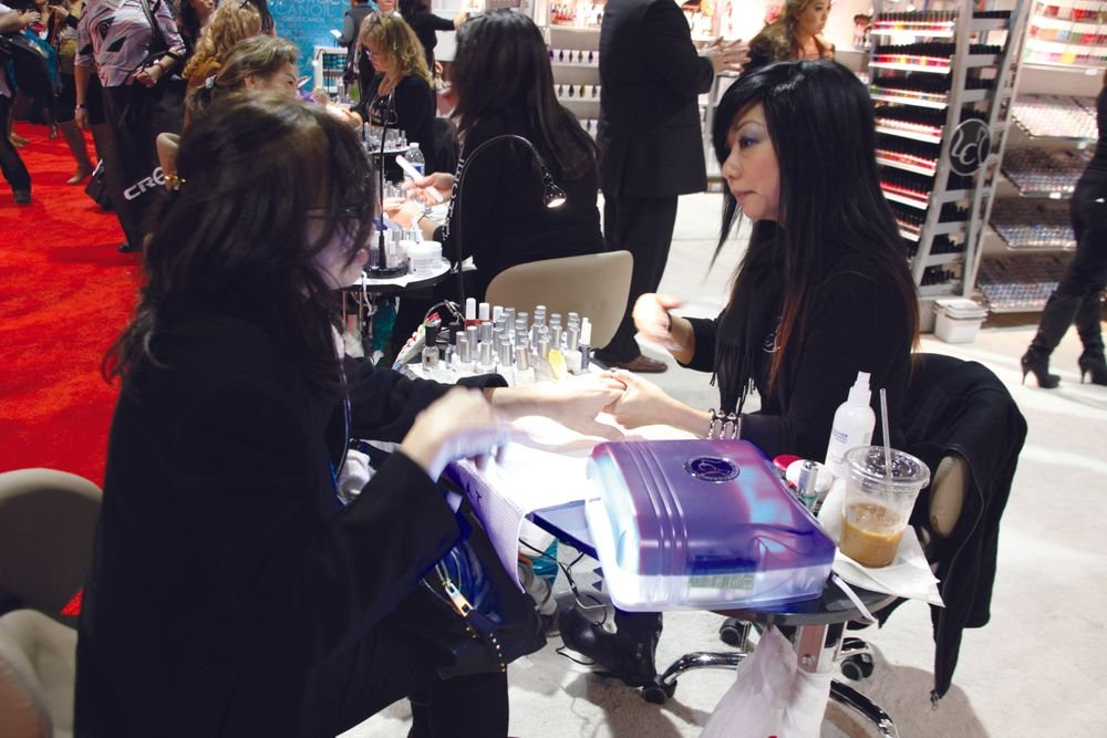 <p>LeChat educator Kristina Hong (right) helped first-time show attendee Hong Nguyen to a demo of LeChat&rsquo;s Perfect Match gel-polish.</p>
