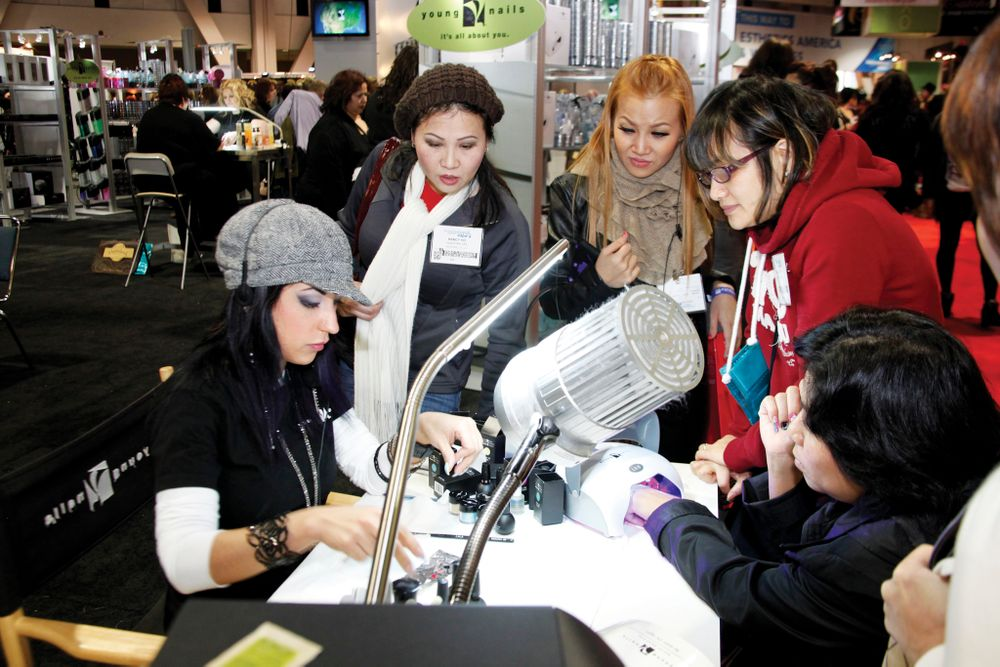 <p>Young Nails&rsquo; Brittany Hogan demonstrates ManiQ gel-polish to a group of show-goers.</p>